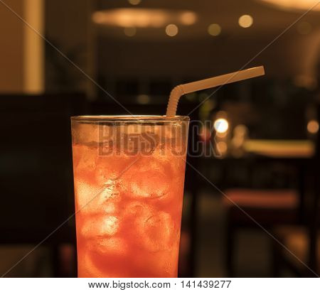 cocktail with ice in the bar background.