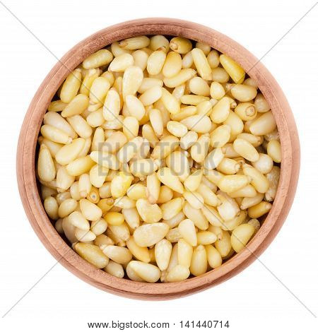Shelled pine nuts in a bowl on white background. Edible seeds of Korean pines family Pinaceae, genus Pinus, in a wooden bowl, isolated, macro photo from above. Pinus koraiensis. Close up.