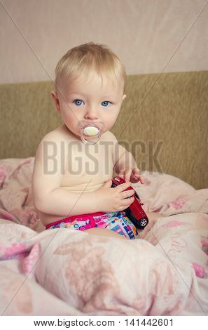 Adorable naked blond baby boy with blue eyes sitting and playing with a toy car in the parents bed. Cute toddler in pink diaper with pacifier. Beautiful baby is sitting on a bed.