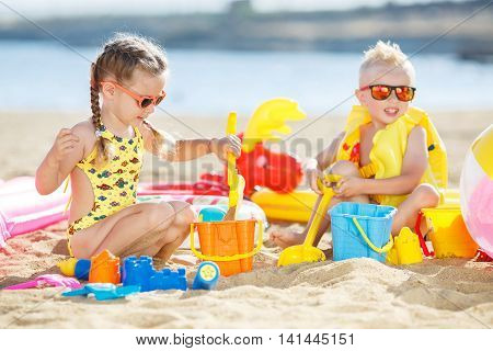 Little girl with pigtails and a little blond boy with short hair,brother and sister,both wearing sun glasses,the girl dressed in a yellow swimsuit,the boy wore a yellow inflatable life vest,sit together on the beach,play in the sand colorful plastic toys