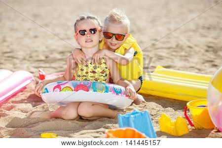 Little girl with pigtails and a little blonde boy with short hair, a brother and sister, both wearing sun glasses, a girl dressed in a yellow bathing suit and multicolored lifeline, the boy wore a yellow inflatable lifejacket, spend time together at the b