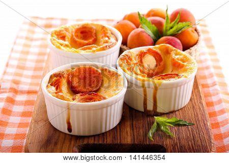 Apricot puddings in ramekins on wooden board