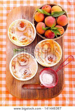Apricot puddings with icing sugar in ramekins top view
