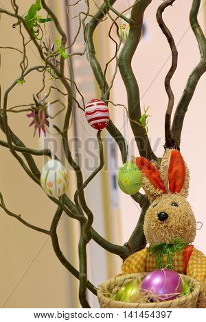 colorful Easter decoration on a corkscrew hazel with Easter bunny and colorful eggs