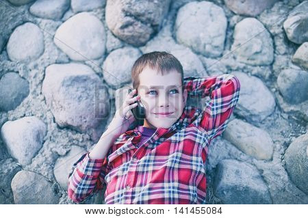 boy smiling and talking on a cell phone. boy lies on a rocky shore, holding a mobile phone to his ear, staring at the sky and smiling. top view