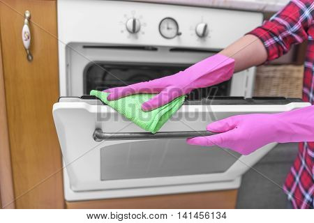 Wash the oven door. Women's gloved hands are washed the dirt. poster