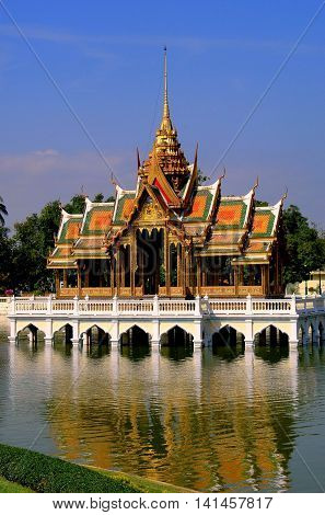 Bang Pa-In Thailand - December 27 2005: The Golden Pavilion (Phra Thinang Aisawan Tippaya) a jewel of Thai architecture with its chofahs gabled roofs and gilded spire sits in the middle of a small lake at the Bang Pa-In summer royal palace
