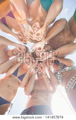 Group of happy friends forming a huddle against sky