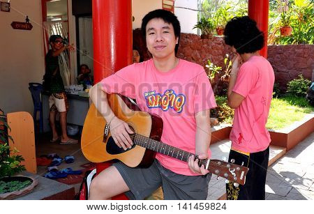 Hua Hin Thailand - December 31 2009: Musician with his guitar entertains by the outdoor waiting room at the Hua Hin Thai Railway Station