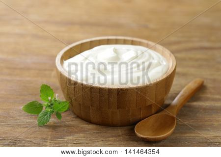 homemade organic sour cream in a wooden bowl