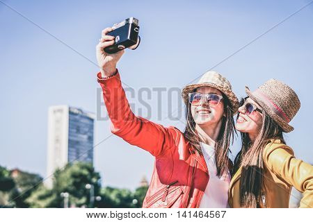 Best friends make selfie photo with old retro camera while traveling across Europe on vacation - Funny outdoor activity of young fashion students away from home - Vintage editing with soft vignette