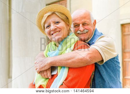 Happy senior couple in love enjoying romantic vacation in Italy - Husband hugging his wife holding a smartphone - Joyful elderly active lifestyle - Main focus on woman Warm vivid filter