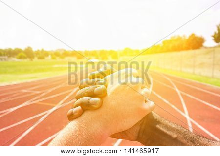 Multiracial runners shaking hands before athletic competition with back lighting - Multi-ethnic people showing respect against racism - Fair competition concept - Soft warm filter