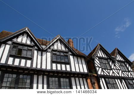 Looking up to the facade and apex of a row of Tudor style houses under a clear blue sky for copy space.