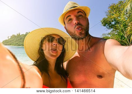Beautiful young couple in love doing selfie on a tropical beach - Tourist taking photo with funny faces - Holidays and vacation concept in summer time - Tilted horizon composition