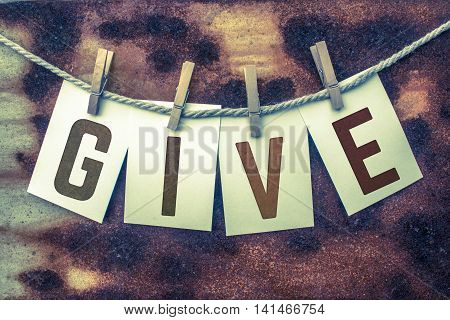 The word GIVE stamped on card stock hanging from old twine and clothes pins over a rusty vintage background.