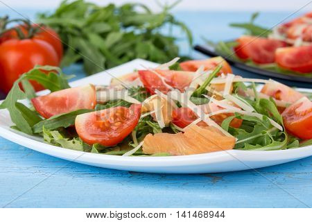 Salmon salad with aragula and cherry tomatoes on white plate on blue wooden background