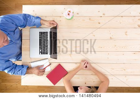 Businessman interviewing a potential job candidate seated at a wooden office table with an open laptop while questioning a young woman over head view with copy space