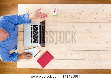 Man welcoming his staff or guests to a business meeting seated at the office table with an open laptop and notes gesturing a greeting with his hand to bid them welcome overhead view