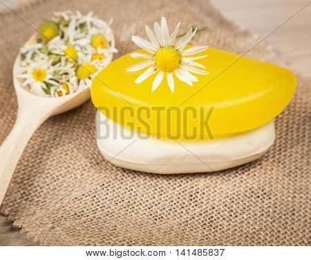 Chamomile handmade soaps, chamomile flowers in a wooden spoon on jute cloth