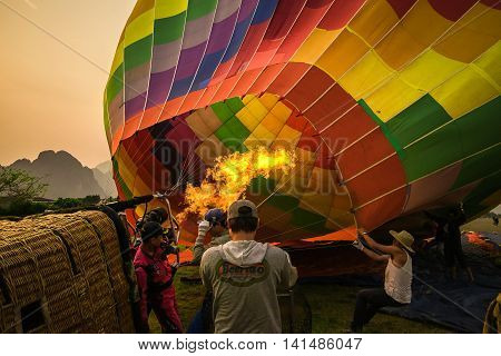 Filling up balloon/ Vang Vieng, Laos - April 29, 2016: Staffs of the tour company are filling one of the balloons for a flight by using the burner that bursts the flame and pushes the hot air inside the balloon.