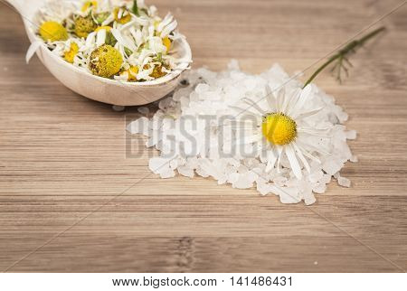 Placer sea salt, chamomile flowers on a wooden spoon on a wooden surface