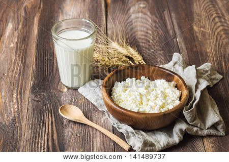 Cottage cheese milk and ears of wheat on rustic wooden background. Dairy products for jewish holiday Shavuot.
