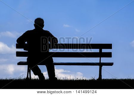 Old Man Sitting Alone On Park Bench Under Tree;