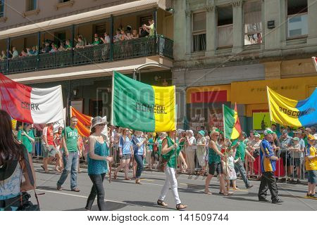 Brisbane, Australia - March 16, 2013; Crowds involved or watching parading Irish in predominant color of green holding regional banners in Brisbane streets on St Paddy's Day