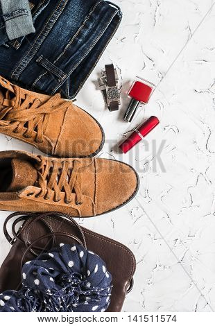 Women's clothing and accessories - suede boots jeans leather bag scarf red nail polish and lipstick. On a light background top view