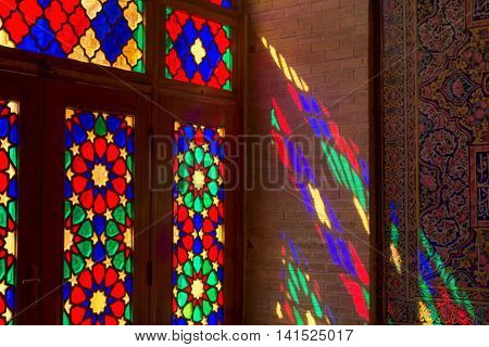 SHIRAZ IRAN - May 3 2016: Detail of the Nasir al Molk or Pink Mosque in Shiraz Iran. The stained glass windows produce a colourful effect on the carpets columns and walls in the morning.