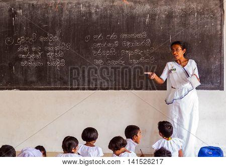 KANDY SRI LANKA - JANUARY 31 2016: Lesson in school Sri lankan teacher writes on the blackboard Tutoress teaches Young girls and boys children in classroom at lesson.