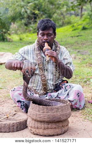 POLONNARUWA SRI LANKA - JANUARY 31 2016: Snake charmer adult man playing on musical instrument before snake at a old basket
