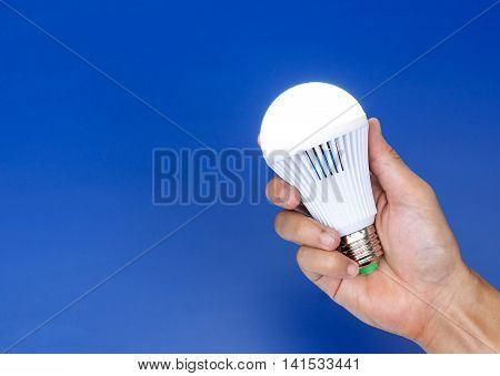 Hand holding a turned on LED light bulb / Using economical and environmentally friendly light bulb concept