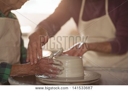 Mid-section of male potter assisting female potter in pottery workshop