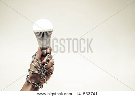 A turned on LED light bulb chained and lock / Something stops new idea / Freedom of thought