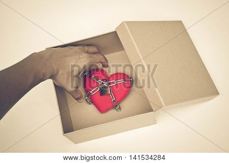 Red heart chained in a paper box / difficult love and obstacle