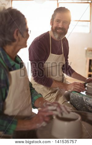 Male potter interacting with female potter in pottery workshop