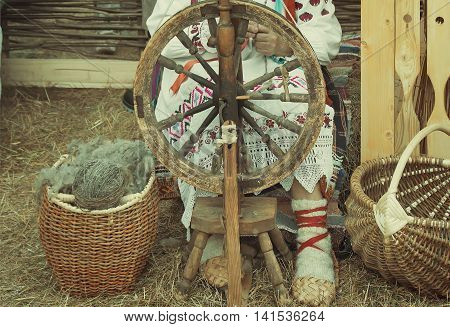 Near an old spinning wheel sits an elderly woman in national costume and worked on it spinning.