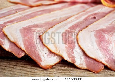 Assorted Slices Of Fat Pink Bacon On Wooden Desk