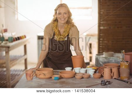 Beautiful female potter leaning on worktop in pottery workshop