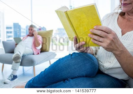 Cropped image of woman reading book with man in background at home