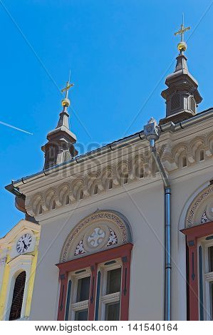 TIMISOARA ROMANIA - AUGUST 5 2016: Architectural decorations at the facade of Serbian Vicariate and towers from Serbian church in Timisoara Romania.