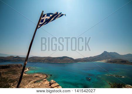 Crete, Greece: aerial view of Gramvousa island and Balos Lagoon. Flag of Greece
