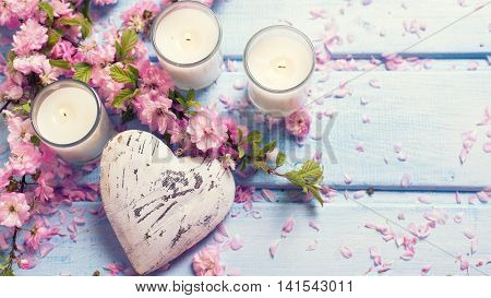 Background with sakura pink flowers decorative heart and candles on blue wooden planks. Selective focus. Place for text. Toned image.