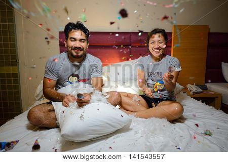 asian couple celebrating new year with fire cracker on bed