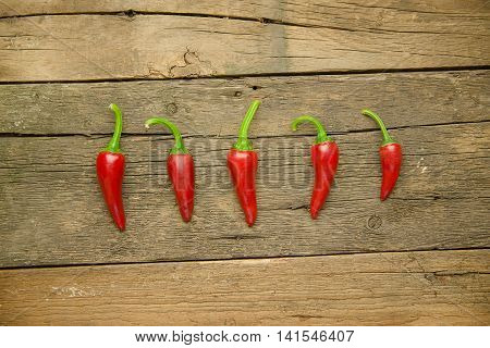 Red hot Chilli peppers on old wooden surface