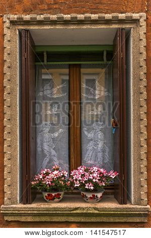 Window with orange colored wall. Nice pink flowers at the window. There is a lacework curtain on window glasses with dancing girl and boy and birds image.Window frame is brown.