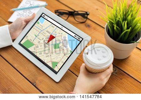 business, navigation, technology, people and advertisement concept - close up of woman with gps navigtor map on tablet pc computer screen and coffee cup on wooden table