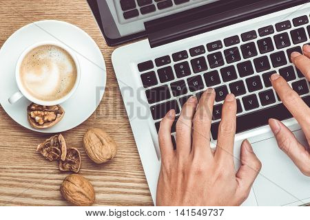 Laptop and coffee cup in male hands on a wooden floor